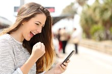 Euphoric woman watching her smart phone in a train station.jpg