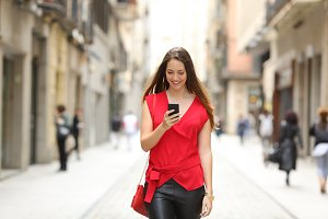 Fashion woman walking and using a smart phone.jpg