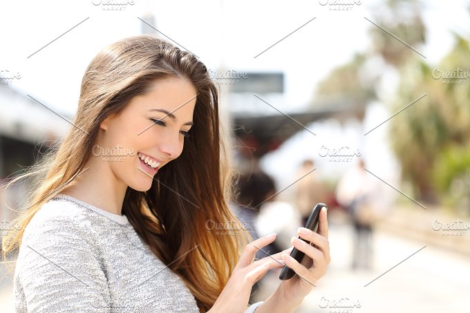 Girl texting on a smart phone in a train station.jpg - Technology