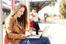 Girl using a laptop while waiting in a train station.jpg
