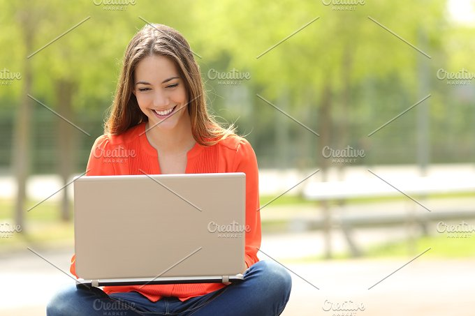 Happy girl working with a laptop in a green park.jpg - Technology