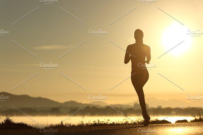 Runner woman silhouette running at sunset.jpg - Sports