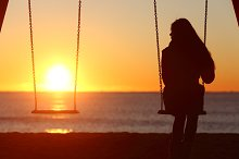 Single woman alone swinging on the beach.jpg