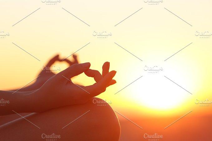 Woman hands exercising yoga at sunset.jpg - Health