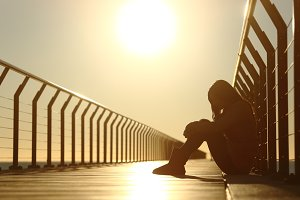 Sad teenager girl depressed sitting in a bridge at sunset.jpg