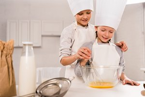 boy with sister in chef hats whiskin