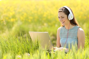 Woman working with a laptop in a field in summer.jpg
