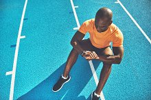 Young athlete sitting on a track che by  in Sports