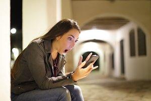 Amazed woman checking phone