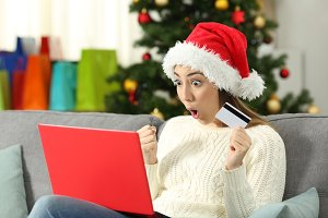 Amazed woman buying gifts on line