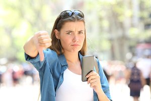 Annoyed woman holding a smart phone