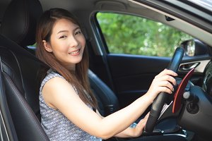 Young asian woman driving a car