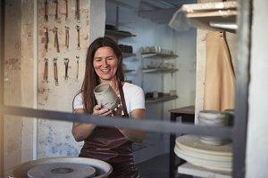 Smiling artisan examining a vase in