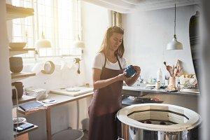 Female artisan inspected glazed pott