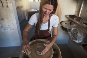 Artisan shaping clay on a pottery wh