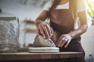 Female artisan weighing blocks of cl