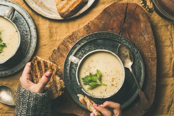Celery cream soup and female hands