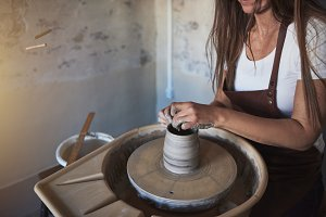 Creative artisan shaping clay on a w