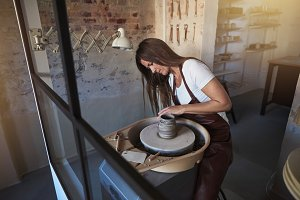 Artisan creatively shaping clay in h