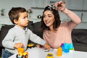 positive woman playing with toy airp