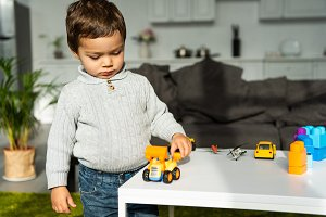 child playing with toy cars at table