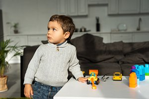 kid playing with toy cars at table i