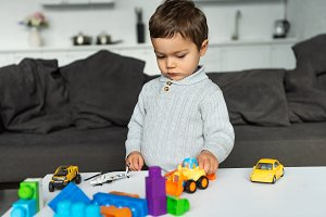 boy playing with toy cars at table i