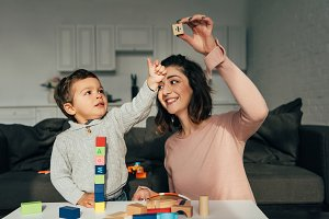 kid and his mother playing blocks wo