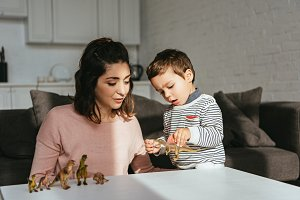 woman and little son playing toy din