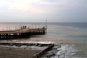 Beach pier with fisherman