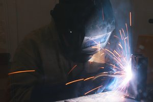 A welder in helmet doing his job