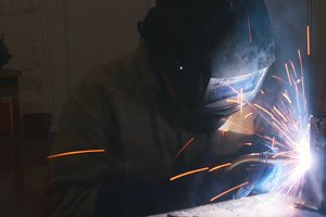 A welder in helmet doing his job