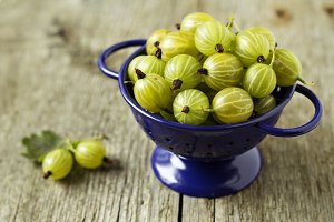 Fresh gooseberries in blue colander