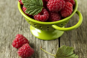 Fresh raspberries in green colander