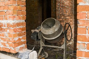 Old grey cement mixer against a