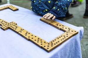 Little kid playing a wooden domino