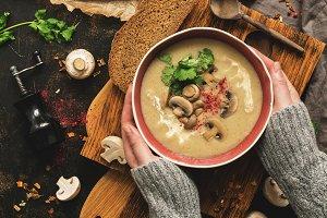 Bowl of mushroom cream soup in woman