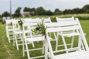 White wedding chairs decorated with