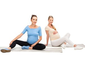 two pregnant women sitting on fitnes