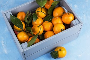 Fresh tangerines in box with leaves