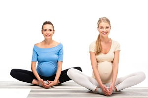 two pregnant women sitting on floor