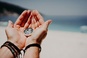 Man's hand holding compass against