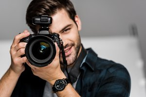 smiling young man photographing with
