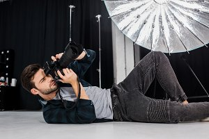 handsome young photographer lying an