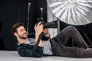 smiling young photographer lying and