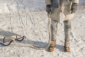 Winter boots on snow near sledge