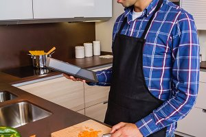 Man in home kitchen looking tablet