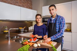 Couple in home kitchen cooking