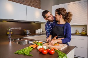 Couple in kitchen hugging and cook