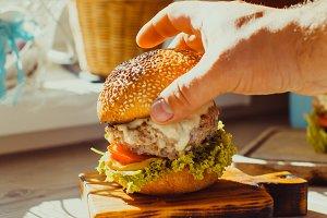Man puts the bun on the beef burger